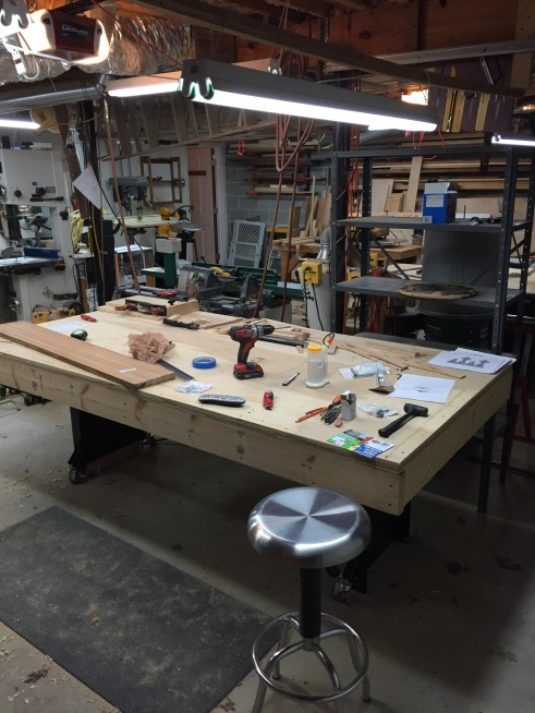 """This is my almost ultimate assembly table. Why? Because it is BIG, 4' x 8' with plenty of room for everything you need, and within arms reach. It's built from 2 sheets of 3/4"""" ply screwed to a 2x6 frame, and it is nearly dead flat. What you can't see is the other reason it's so special. It sits on a Noden Adjust-A-Bench leg set that adjusts height wise from below my waist to chest height (I'm 5'11""""). It's the better part of $500 and is built from heavy guage steel, but is worth every penny. I built my own stretchers and caster set. It's remarkably solid too. I would not trade this thing for the world!"""